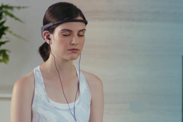 woman meditates while wearing the Muse headband