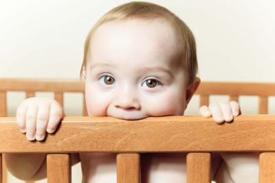 teething baby chews on crib