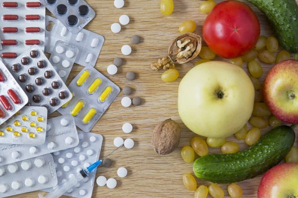 customized 3D printed supplement pills next to the fruits and vegetables they replace