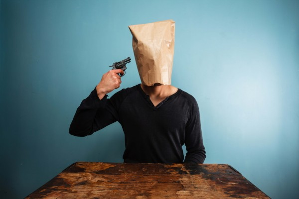 man with gun pointed at bag over his head