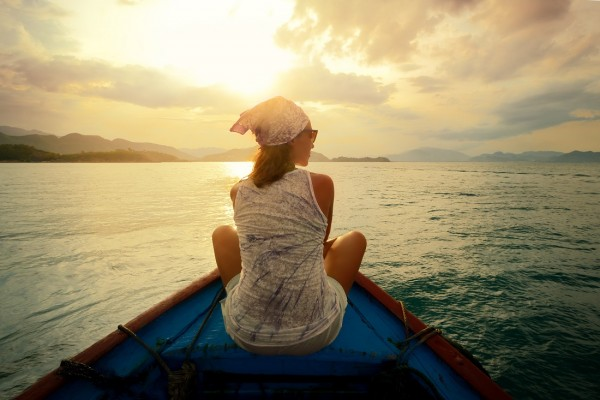 woman alone on boat at sunset