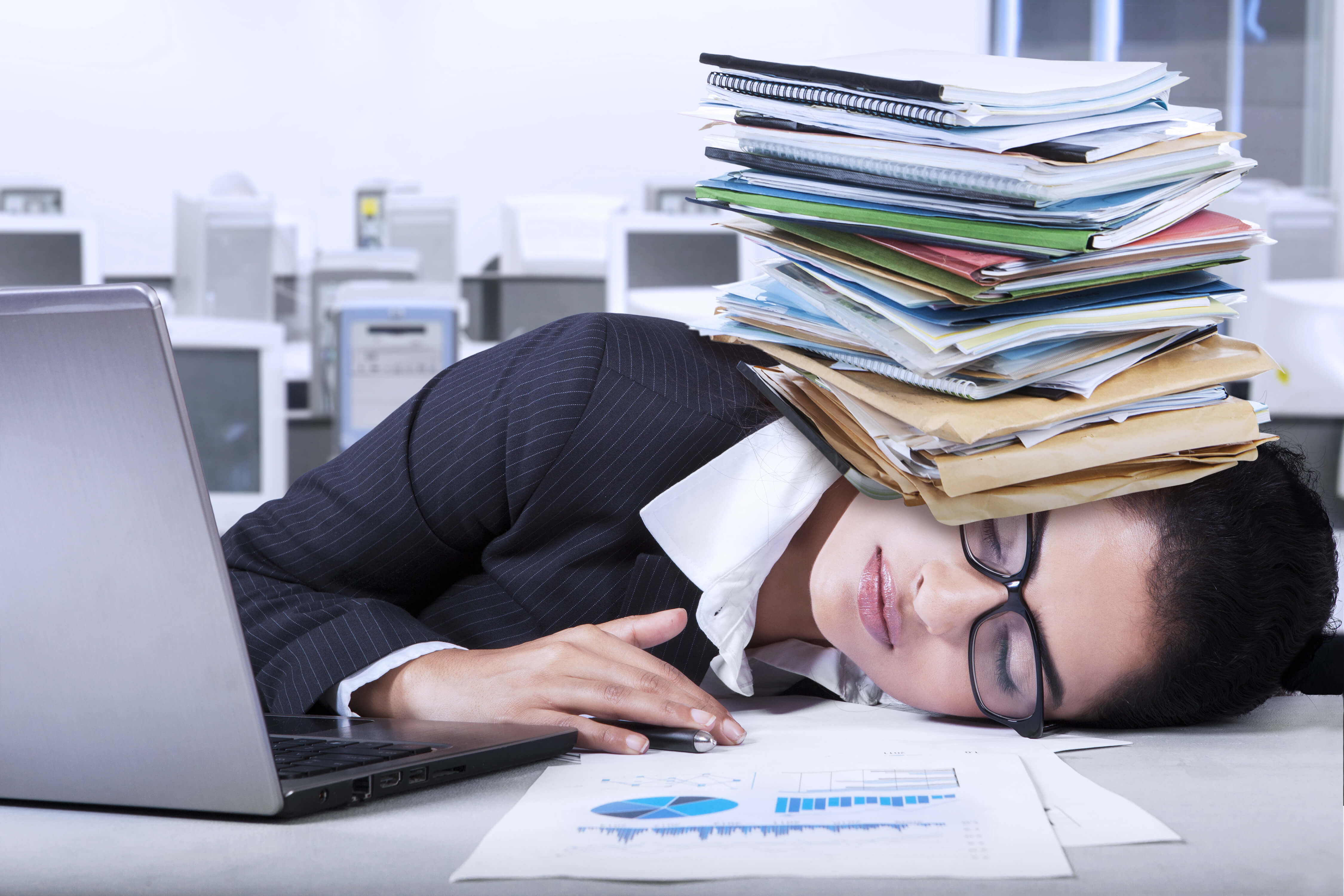 woman sleeps at her desk with piles of paperwork on her head