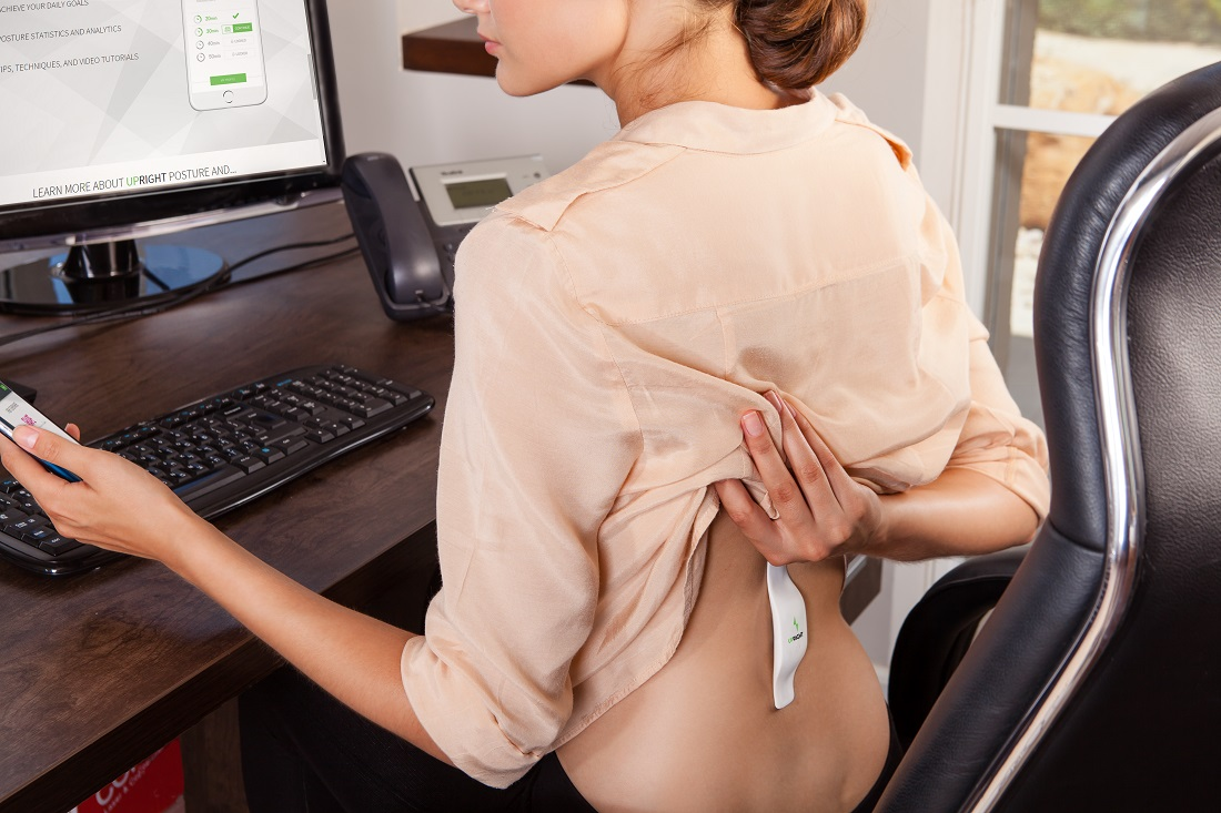 Upright wearable posture trainer worn by woman at desk
