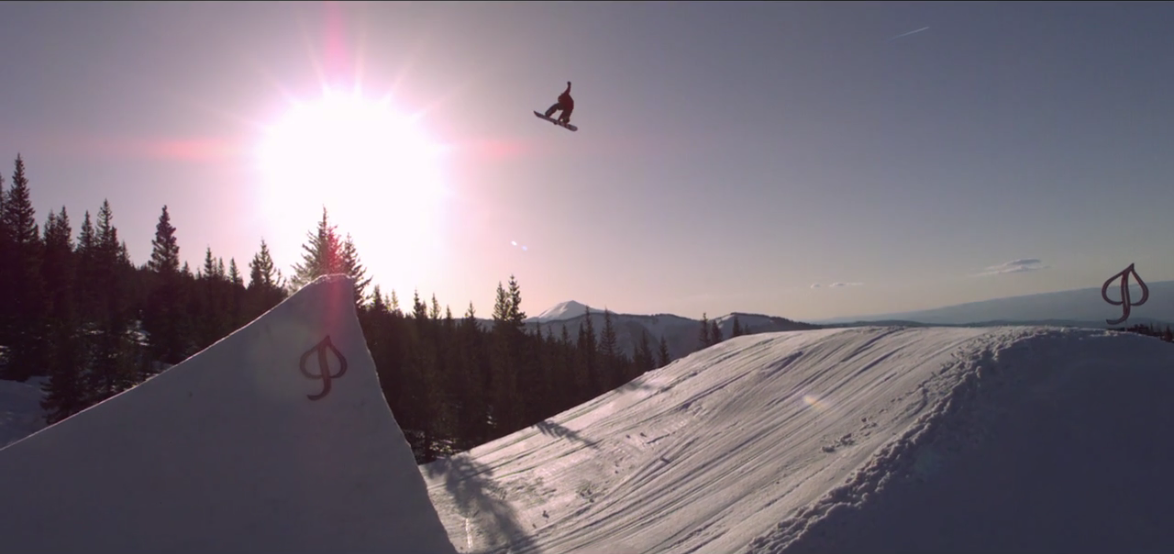 drone filming a snowboard jump