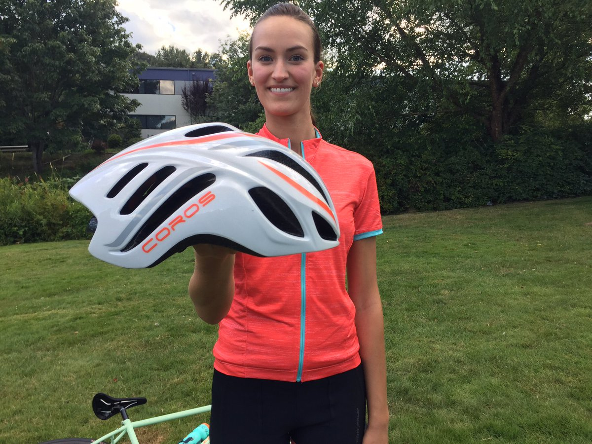 woman holds Coros smart cycling helmet with headphones