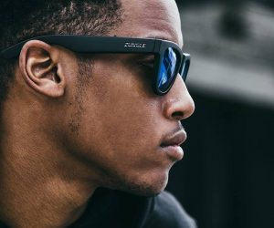 man listens to music without headphones using bone conduction sunglasses