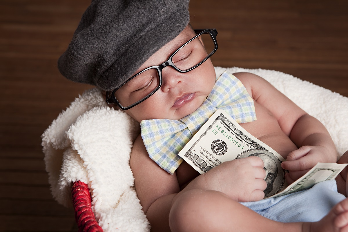 baby holding cash from his universal basic income