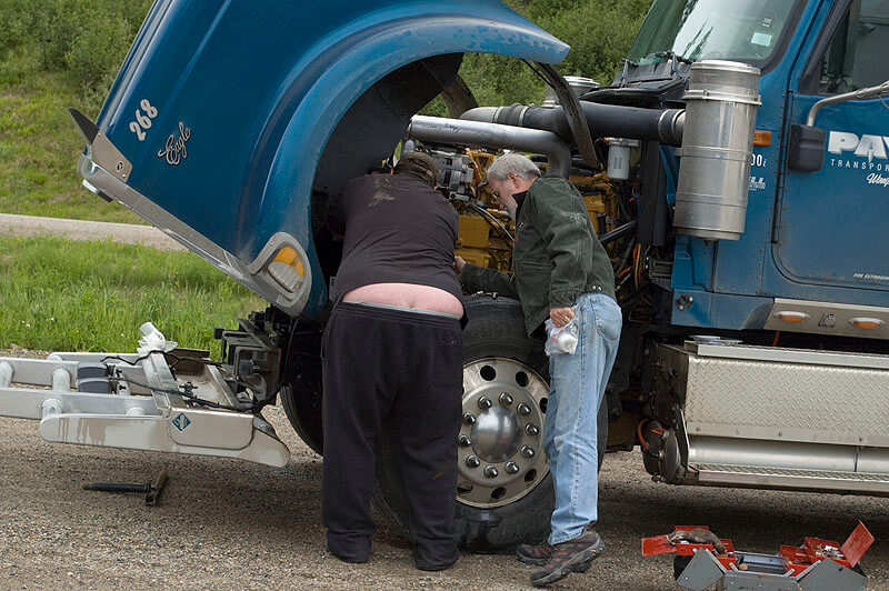 broken-down semi being repaired by mechanic on the roadside