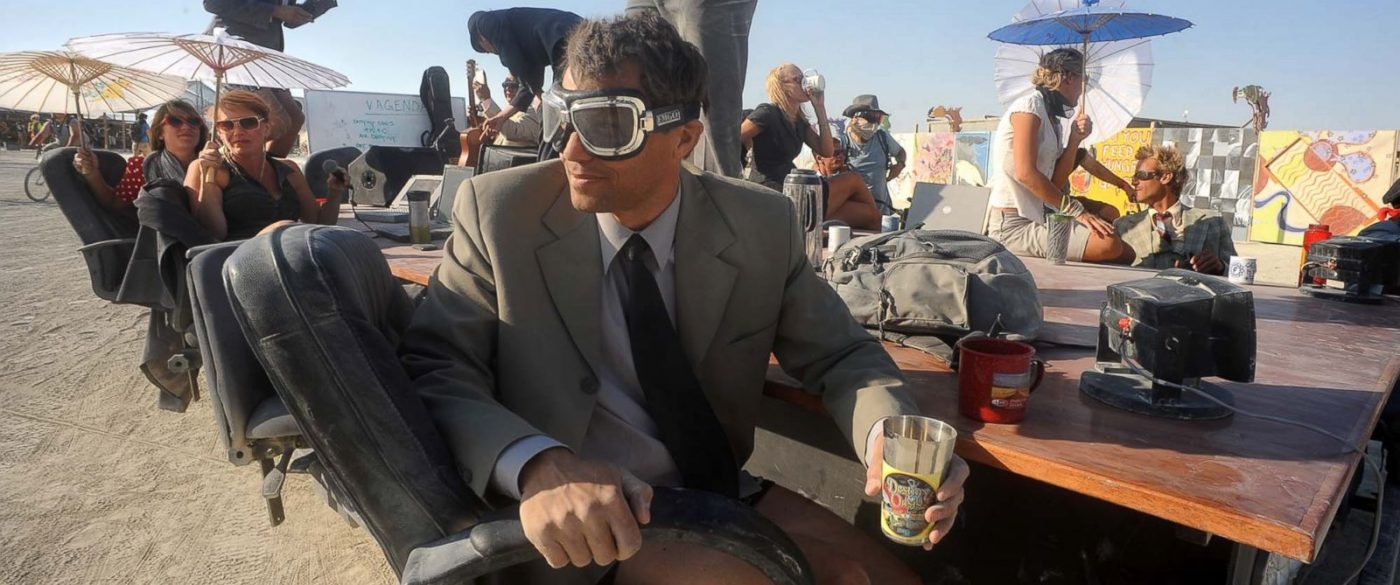 Burning Man board room on the beach with man in suit, shorts, and googles