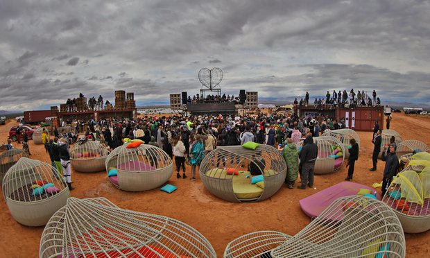 scene from Burning Man 2016 with tech elite gathered around sleeping pods and a stage