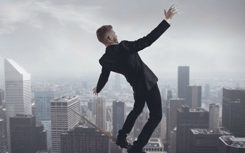 man balencing on tightrope over office building representing eSignature integration