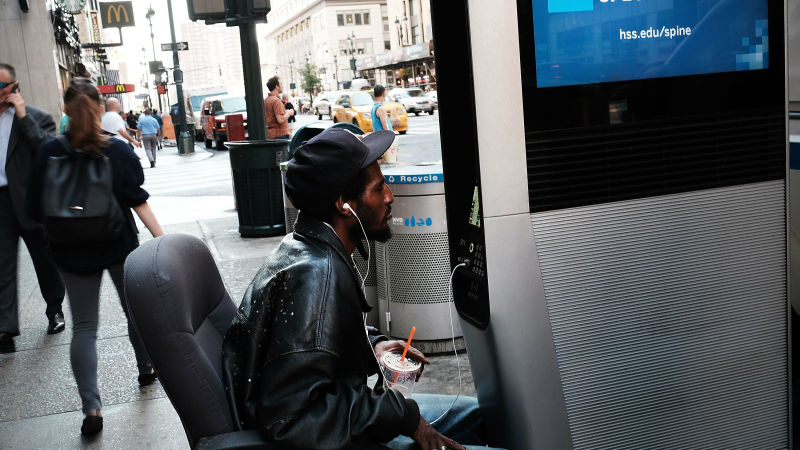 homeless man using NYC free internet kiosk while sitting in an office chair