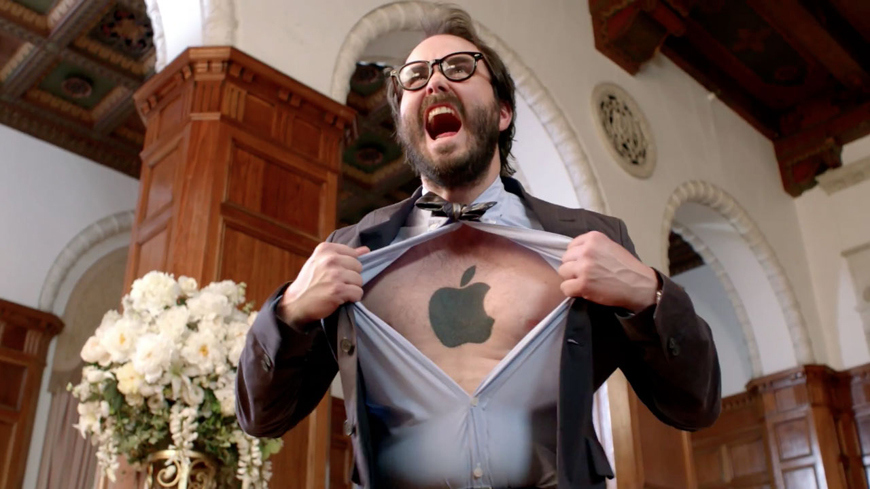Apple fan boy ripping open his shirt to reveal an Apple logo tattoo