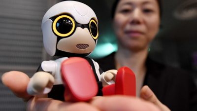 woman talks with a Toyota Kirobo Mini robot companion
