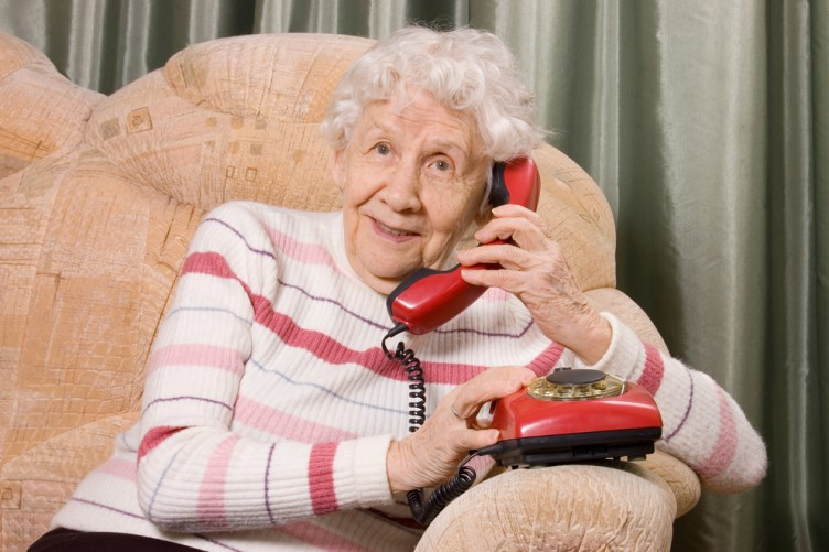 elderly woman attempts to do mobile banking with a rotary phone