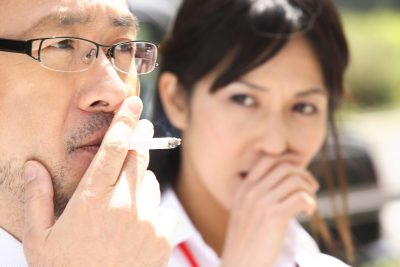 Japanese man smoking outside of smoking booth