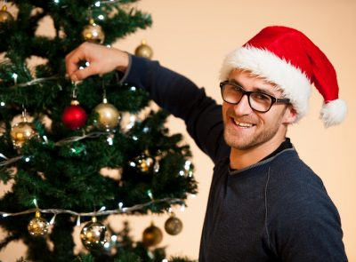 professional Christmas decorator hanging bulb on tree