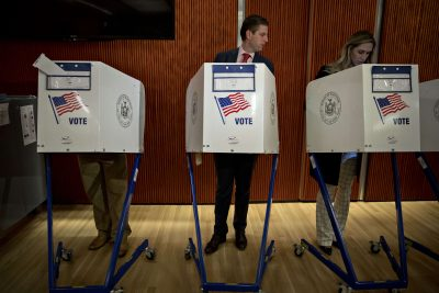 Eric Trump voting on election day by looking at his wife's ballot